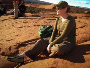 Abby soaks up the sun at Delicate Arch.
