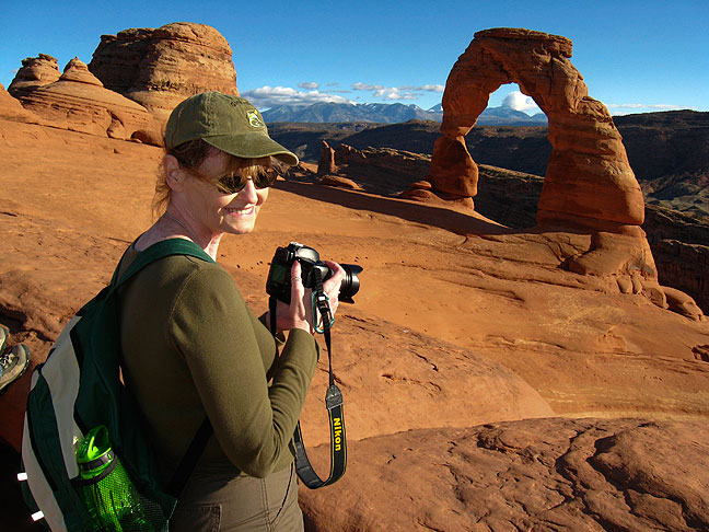 Abby smiles in the warm autumn sunshine at Delicate Arch in Arches National Park