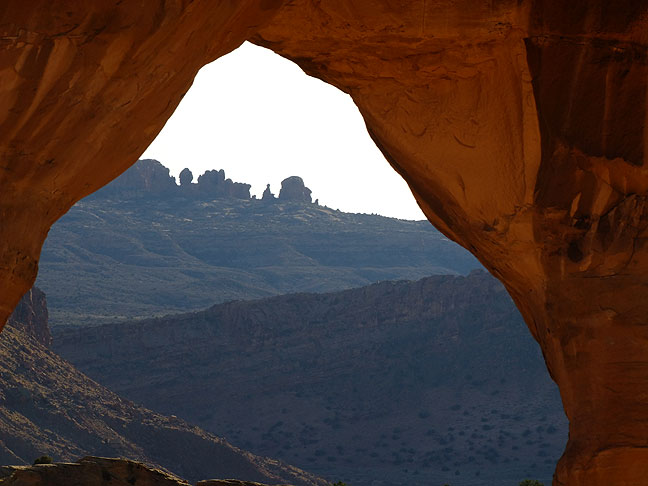 This view looks through the opening of Delicate Arch to the Windows section of Arches National Park.