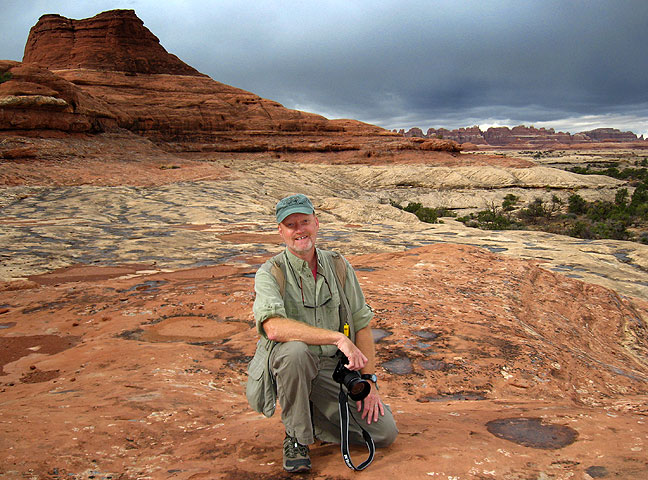 Posing on a slickrock bench as storm clouds approach at Canyonlands (Photo by Kevin Swanson).