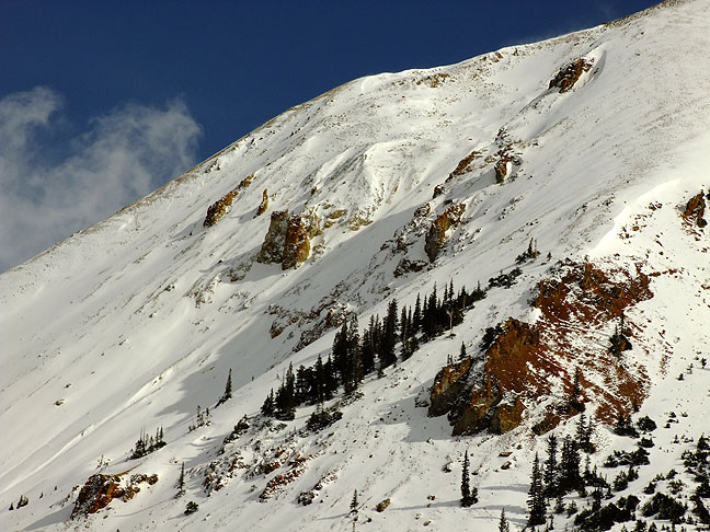 Snow clings to the steep slope of a 14er in the San Juan Mountains of Colorado along the &quot;Million Dollar Highway&quot; between Ouray and Silverton, Colorado.