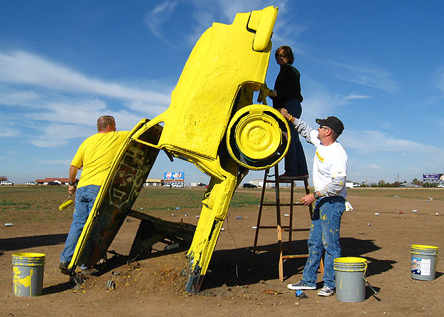 Volunteers from the LiveStrong Foundation paint the cars at the Cadillac Ranch yellow, LiveStrong's color.