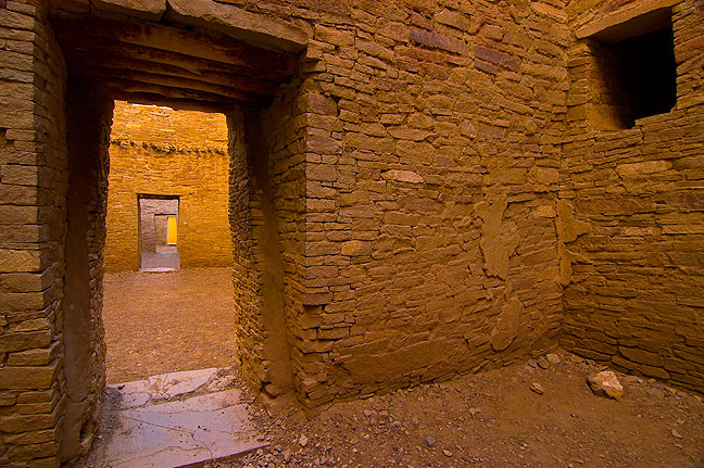 Pueblo Bonito: intricate, ancient masonry doorways lit by soft, glowing light.