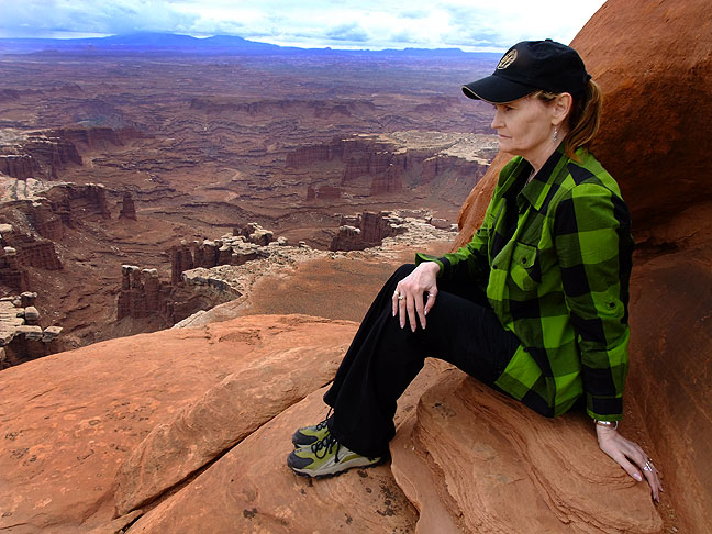 Abby takes in the view at the end of the White Rim Overlook trail in the Island in the Sky District at Canyonlands National Park.