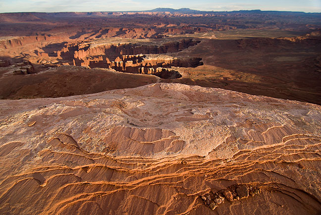 Layered sandstone at Canyonland's Grand View Point, with Monument Basin below and the Needles district and the Abajo Mountains in the distance.