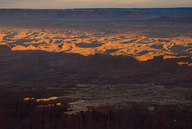A streak of light crawls across the complex formations below Grand View Point, Canyonlands.
