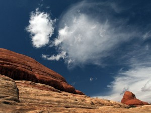 Brilliant clouds swiftly float past bold sandstone benches as we travel farther down the Peek-a-Boo trail.