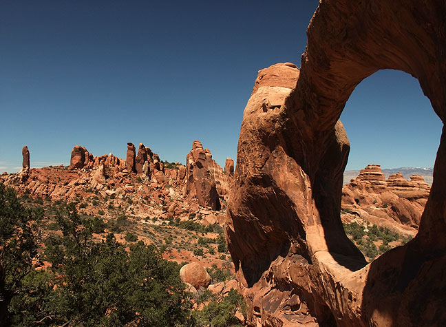 Near the northern reaches of the Primitive Loop trail in the Devil's Garden section of Arches; Double-O Arch is shown in the right side of the frame, with the Dark Angel spire visible on the left side of the frame.