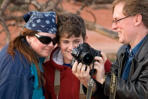 """Deb and David look at the display on Robert's camera on what can only be described as a """"Kodak moment"""" while they take turns photographing each other at Grand View Point, Island in the Sky district, Canyonlands National Park."""