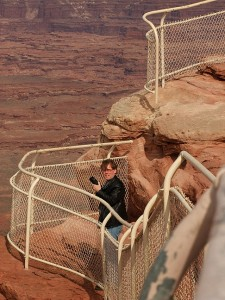 Robert prowls around the short trail at the Needles Overlook in the Canyon Rims Recreation Area. The fence protects visitors from a 1200-foot Wingate sandstone cliff.