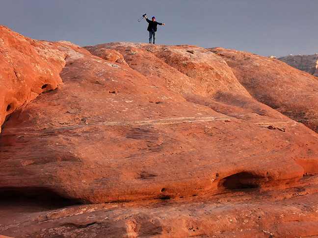 Elated by a breathtaking sunset and struggling to keep his balance in driving winds, Robert raises his arms as the last light leaves the Squaw Flat area at Canyonlands.
