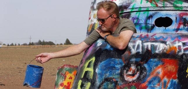 The author poses with a can of blue paint at the Cadillac Ranch.