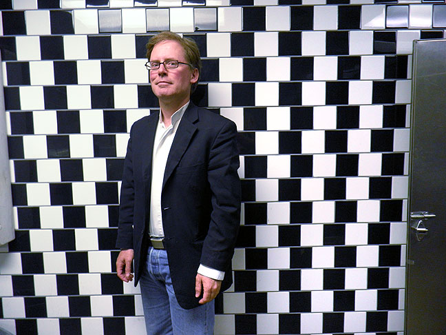 Robert poses with some bathroom tiles arranged to create a classic optical illusion.