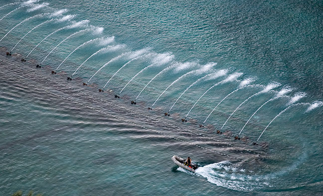 A worker uses a boat to inspect the Bellagio Fountains prior to their evening performance.