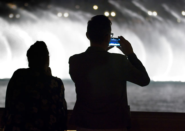 A visitor uses a smartphone to photograph the Bellagio Fountains.