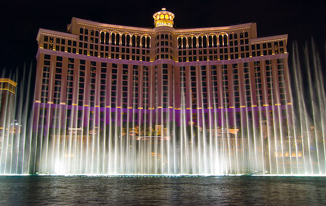This classic view of the Fountains shows the Bellagio Hotel with its changing-color lights.