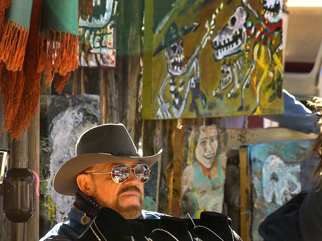 An artist waits to sell paintings, Santa Fe, New Mexico.