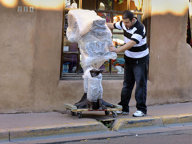 A man moves a sculpture, wrapped in bubble wrap, down a Santa Fe street. When I first saw it, I thought it was an Apollo astronaut.