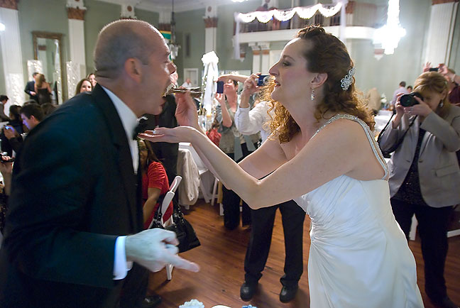 """Nicole feeds a bite of """"wedding cake"""" (doughnuts) to Tracey in the time-honored custom."""