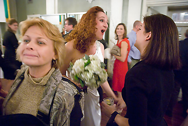 An elated and gregarious bride mingles and laughs with the crowd.