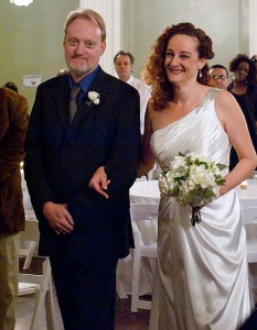 """Nicole beams as I escort her down the center aisle. At her request, when asked who gives away the bride, I said, """"In honor of our mother and father, I do."""""""
