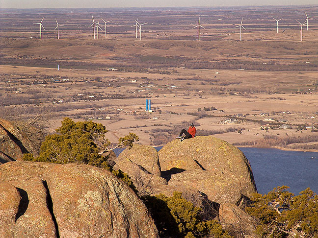 A visitor climbs on a rock at the summit of Mount Scott with the Blue Canyon Wind Farm in the distance.
