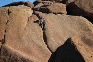"Descending from Sitting Rock can be a little trickier than getting up. You can see me doing an improper ""face first"" descent on this crack, but it just somehow works out better."