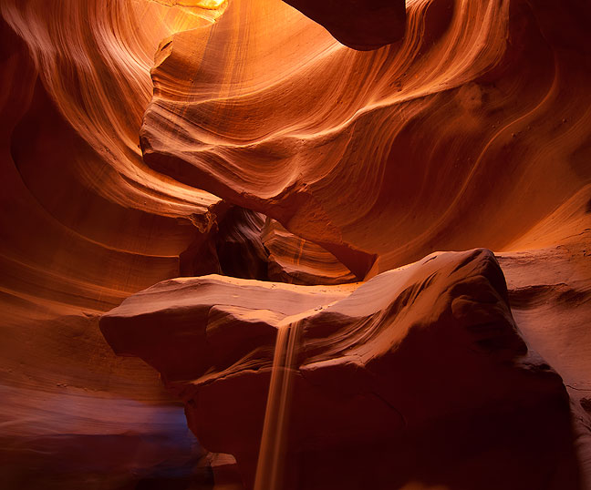 Sand flows down a stone in Antelope Canyon, thrown there by our guide using a large ladle.