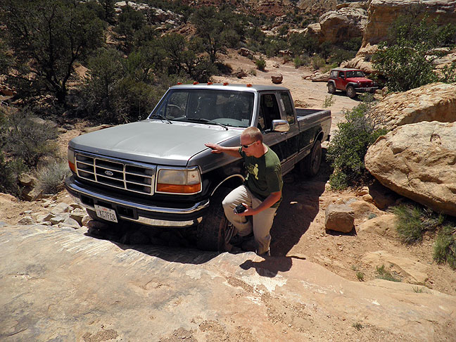 "Dennis Udink gets out of his truck to survey a particularly difficult section of ""road"" in the Teapot Rock section. Note the numerous scratches in the stone in front of Dennis' bumper."