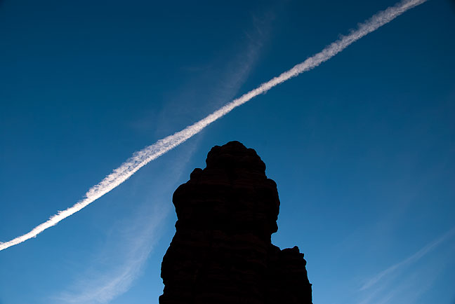 A jet contrail drifts across the silhouette of Standing Rock in The Maze.