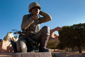 "This bronze memorial to the legendary Navajo ""Code Talkers"" at Window Rock, Arizona stands about 12 feet tall, with the Window Rock itself, a large natural arch, in the background."