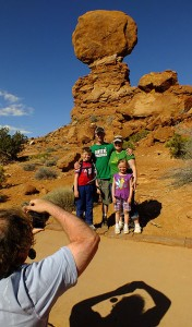 Jim photographs a family with their camera at Balanced Rock in Arches National Park, one of many visitors for whom he volunteered his services.