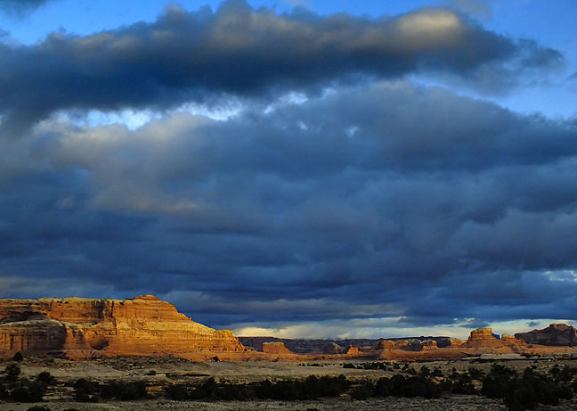 Brooding clouds hang over brilliant mesas as sun sets at Canyonlands.