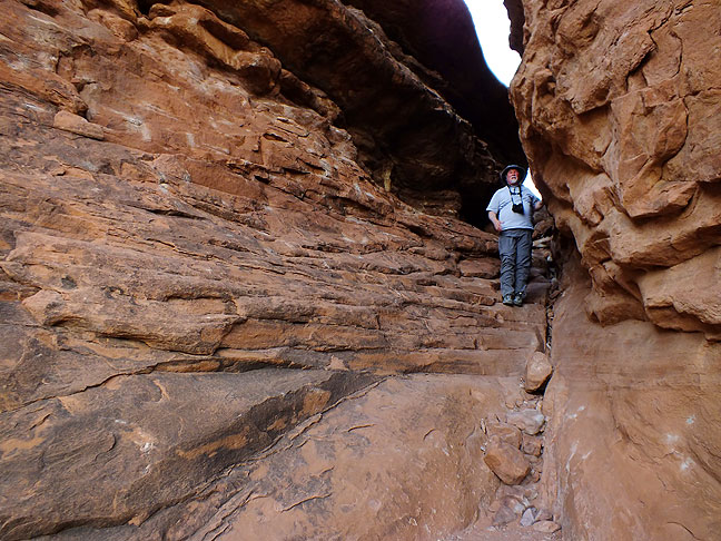 Place of emergence: Jim walks through a crack on the Squaw Flat trail at Canyonlands.