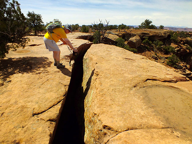 Jim holds his camera near the ground as he photographs a deep fissure along the Murphy Point trail.