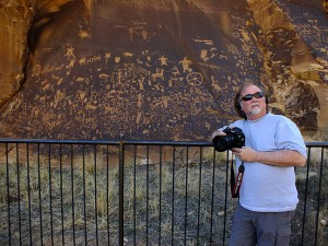 Newspaper photographer Jim Beckel poses at Newspaper Rock.