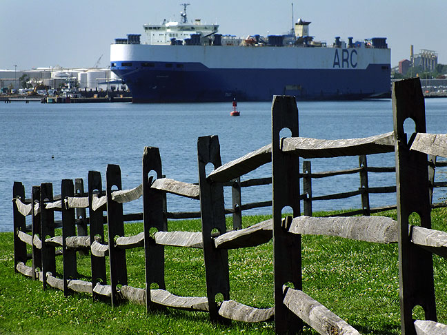 A fence creates an eyeline to a cargo ship in the harbor near Fort McHenry.