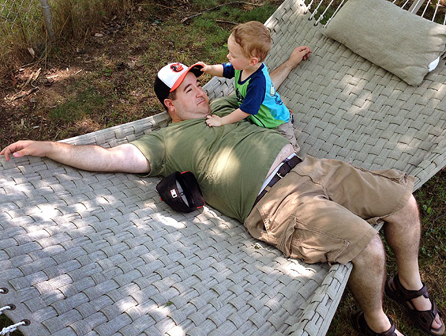 Tom and Paul play on the hammock in their back yard. Tom is a very natural, easy-going dad.