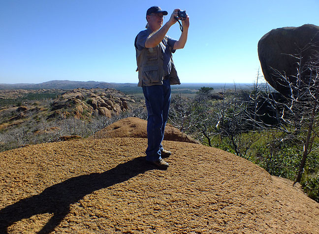 Michael takes aim at Lock Rock from a smooth granite outcropping.