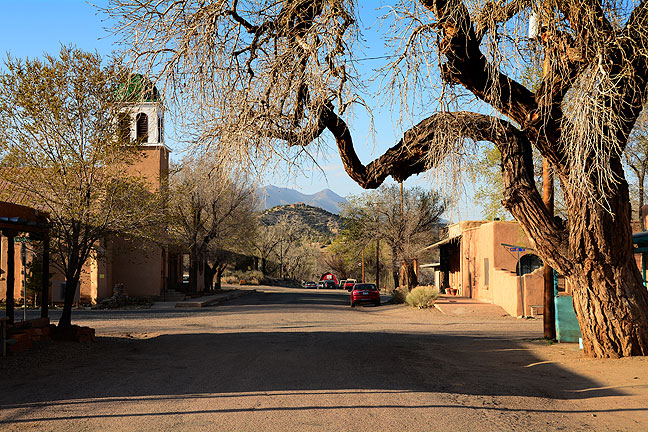 Morning light shines on an empty street in Los Cerillos, New Mexico. Moments after I made this image, I greeted a nun, who frowned at me and walked away.