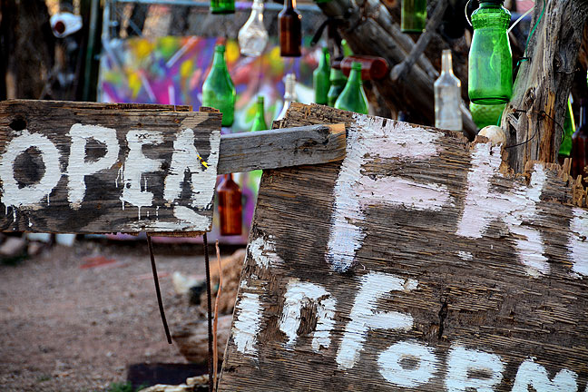 "Hand-painted signs, hundreds of bottles, and the signs ""Come in"" and ""No Trespassing"" adorned this roadside photo op on New Mexico 14."