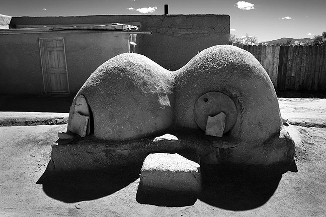 A double kiln stands in bright midday sunshine at Taos Pueblo.