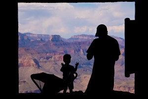 A small boy and his father look at the Grand Canyon from inside the watchtower at Desert View.