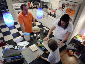 Tom and Chele help Paul decorate cookies to leave out for Santa on Christmas Eve.