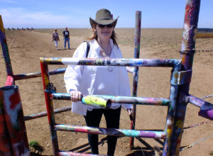Abby squeezes through the gate at Stanley Marsh's Cadillac Ranch in Amarillo, Texas.