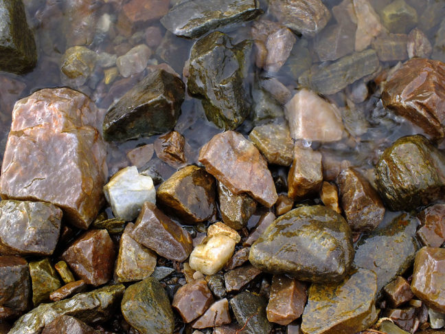 Waters of the Rio Grande lap against stones on the east bank.