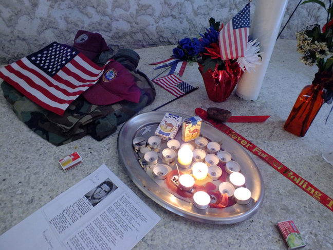 Lit candles and flags sit on the floor at the front of the Vietnam Veterans Memorial Chapel.