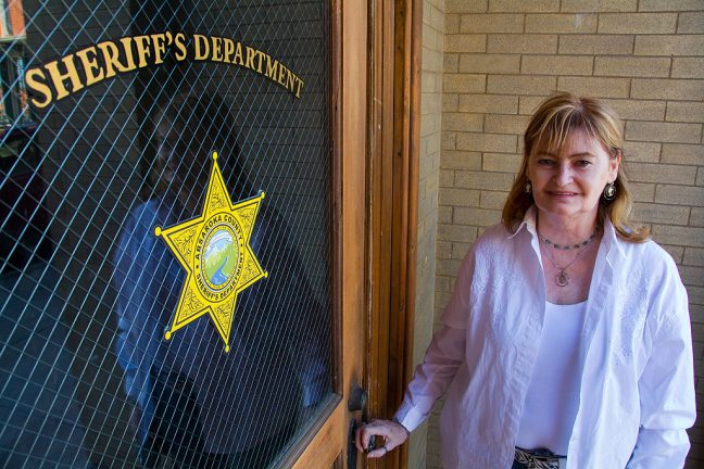 Abby poses at the door in Las Vegas, New Mexico's Old Town Plaza that is the set for the Absaroka County Sheriff's Office in the television series <i>Longmire</i>.