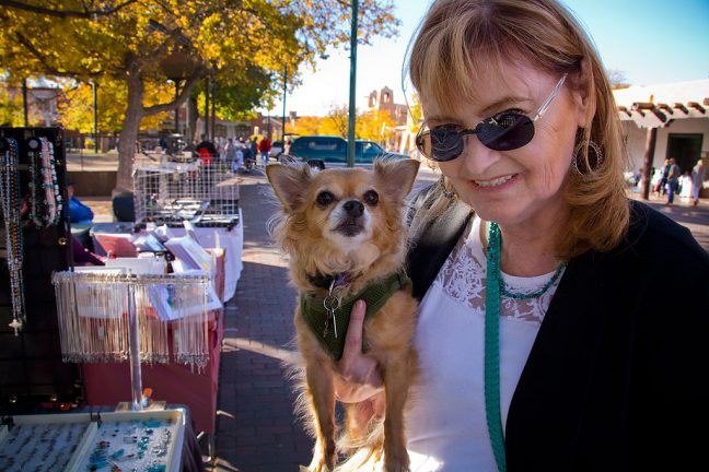 Abby holds her dog Sierra and smiles at me as she buys a piece of jewelry from a Santa Fe Plaza vendor.