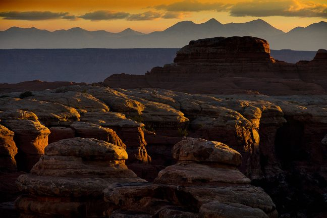 Deep, brooding first light shines steeply across the Cedar Mesa Sandstone of the Chesler Park Trail at Canyonlands.